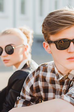 Boy and girl in sunglasses looking away from each other