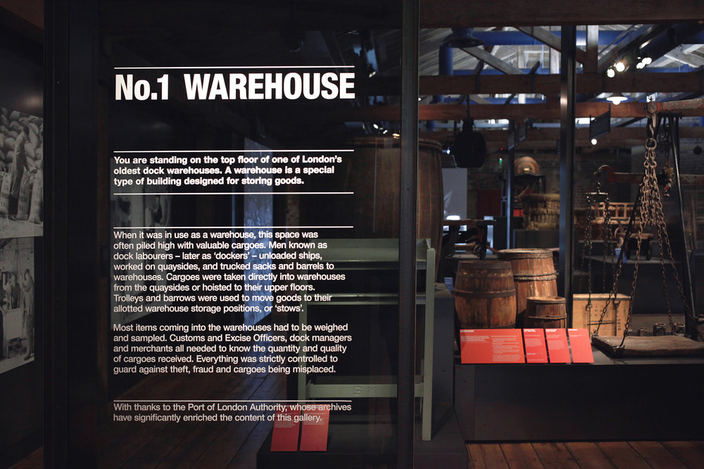 No.1 Warehouse   Museum graphics, Museum of London Docklands, 2016   No1. Warehouse is a permanent gallery housed within the Museum of London Dockland grade one listed building. Our design approach echoes the graphic and raw materiality of old signage previously found in warehouses. Industrial elements such as black steel and glass are combined with bold colours to rouse this beautiful space.  Project completed with Plaid London