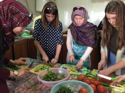 Rowyada, Bretta (team member), Mirvat, and Maddie (team member) making Taboulah.