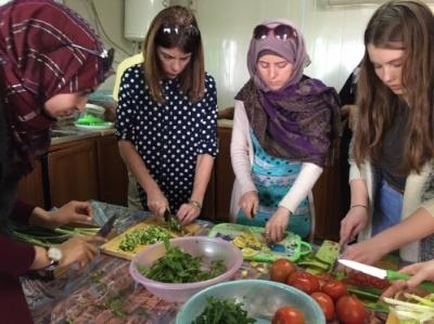 Rowyada, Bretta (team member), Mirvat, and Maddie (team member) making Taboulah.