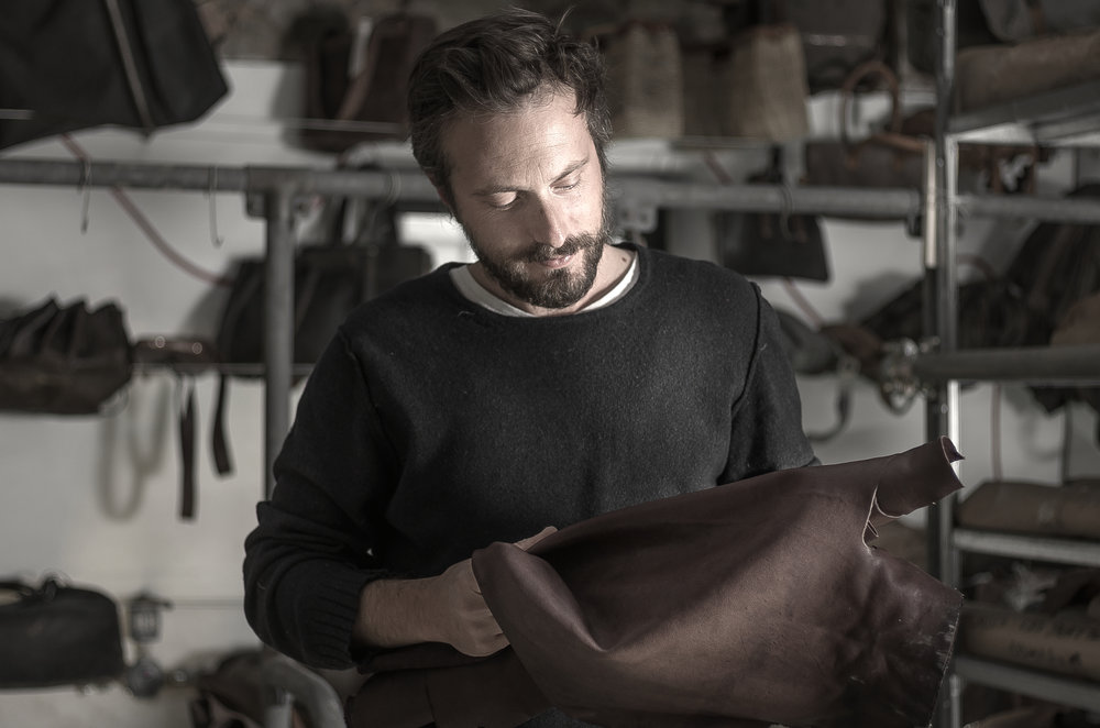 Tommaso inspecting the raw leather.To