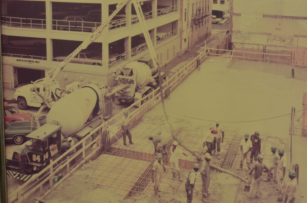 This picture shows the construction of the Commercial National Bank parking garage job in 1976. Notice the Crane Carrier concrete truck with the half cab.