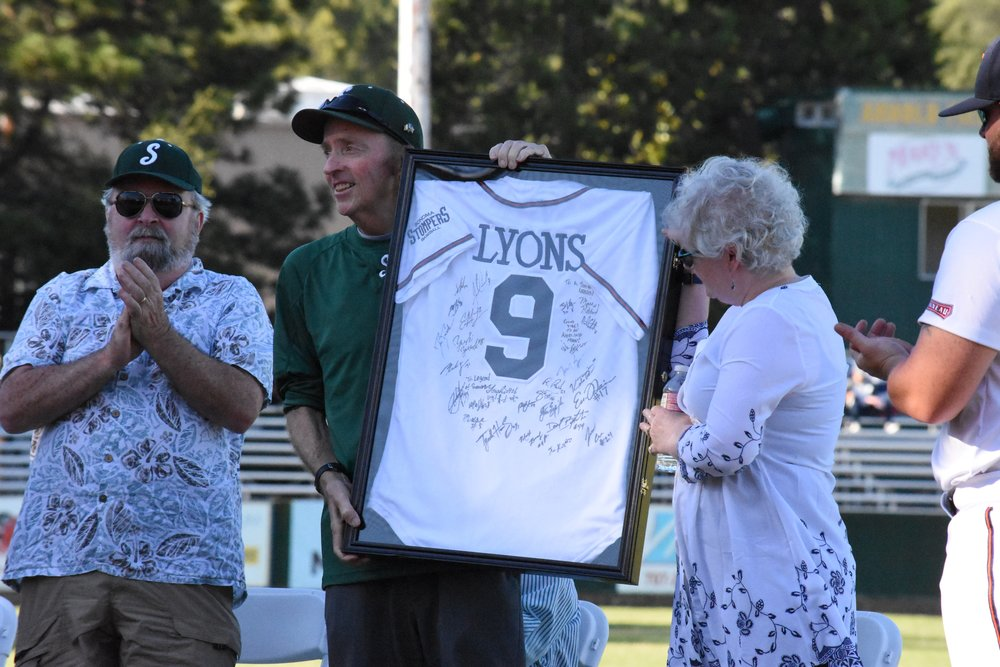 Don Lyons (center) accepts a gift from the Stompers organization during a pregame ceremony Wednesday. (James W. Toy III / Sonoma Stompers)