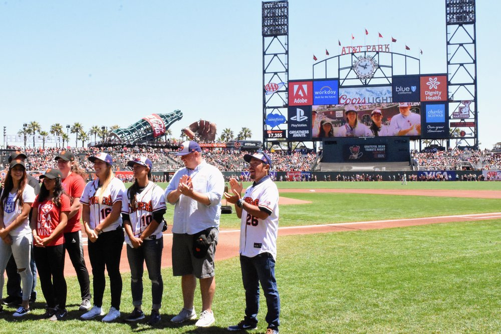 Stacy Piagno, Kelsie Whitmore, Theo Fightmaster and Takashi Miyoshi stand alongside the Women's Deaf National Soccer Team during a pre-game ceremony at AT&T Park on Sunday. (James W. Toy III / Sonoma Stompers)