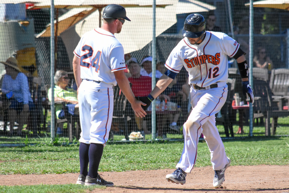 Kenny Meimerstorf (12) is greeted by manager Zack Pace (24) after hitting a solo home run in the seventh inning of the Sonoma Stompers game against the Martinez Clippers, August 5, 2018 in Sonoma, Calif.(James W. Toy III / Sonoma Stompers )