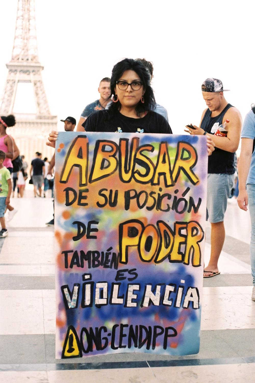 """Luz Ccasihue Alcántara, 30 años. La estudiante me explicó también la pancarta que llevó al plantón: """"Actualmente, ciertas ONGs en Perú, reducen la participación de las mujeres a «mano de obra barata » (promotoras, del asentamiento humano en el que se desarrolla el proyecto, pagadas a la mitad del salario que recibe el personal de la ONG). Acentuando de esa manera los procesos de exclusión, y de pobreza cuando su razón de ser es favorecer la participación de mujeres en Proyectos de Desarrollo Sostenible. Ante esta situación, lo que nos queda por preguntarnos es que si acaso ciertas ONGs no estarían contribuyendo a perpetuar la desigualdad de género, y a la explotación laboral de mujeres que se encuentran en situación de vulnerabilidad? Es que acaso no es éste un acto de violencia? """" *scroll down for the caption's translation."""