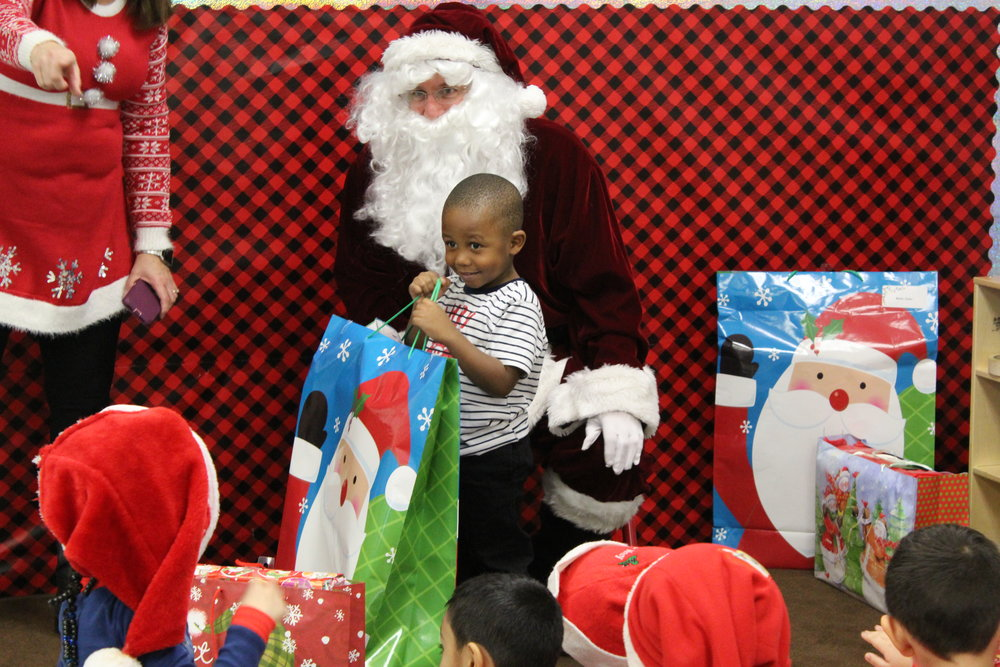 "A child at CYC-CENTRO NUESTRO poses with the ""Xerox Santa"" in December 2018."