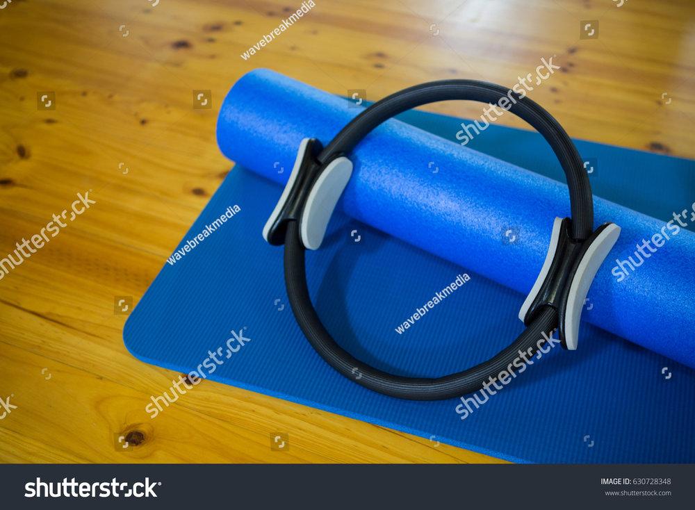 stock-photo-pilates-ring-and-exercise-mat-kept-on-wooden-floor-in-fitness-center-630728348.jpg