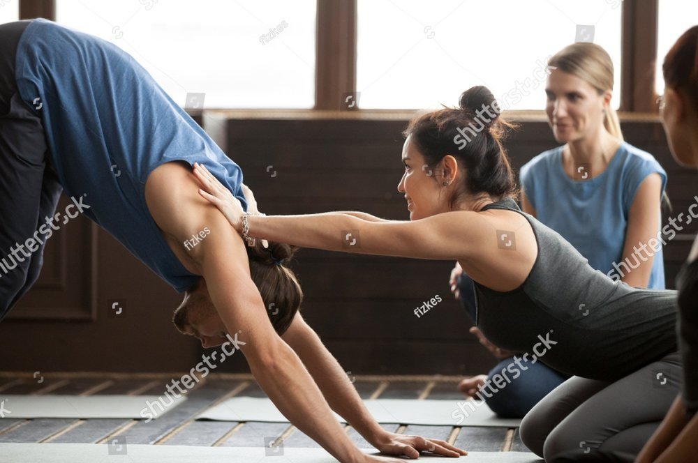stock-photo-smiling-yoga-teacher-or-pilates-instructor-helping-young-man-to-stretch-muscles-holding-hands-on-1018506292.jpg