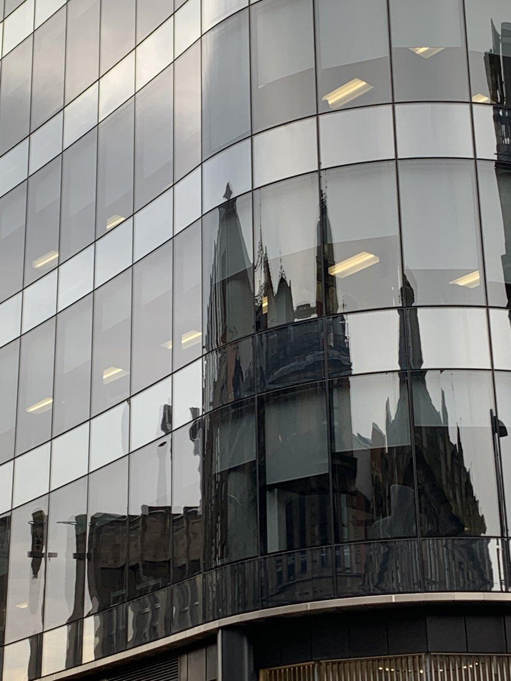 Ancient architecture reflected in modern windows. Glasgow, Scotland