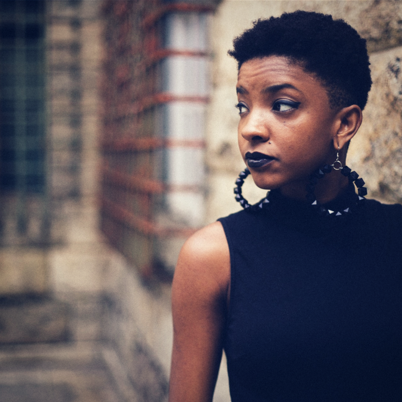 Image Description: A black girl in a black top with a TWA looking towards her right while walking through a city.
