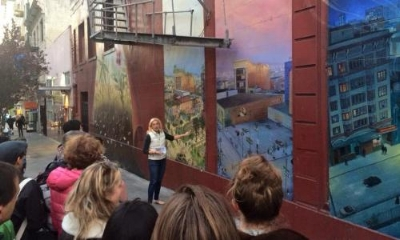 Mona Caron exhibiting her mural during the Tenderloin museum's walking tour.