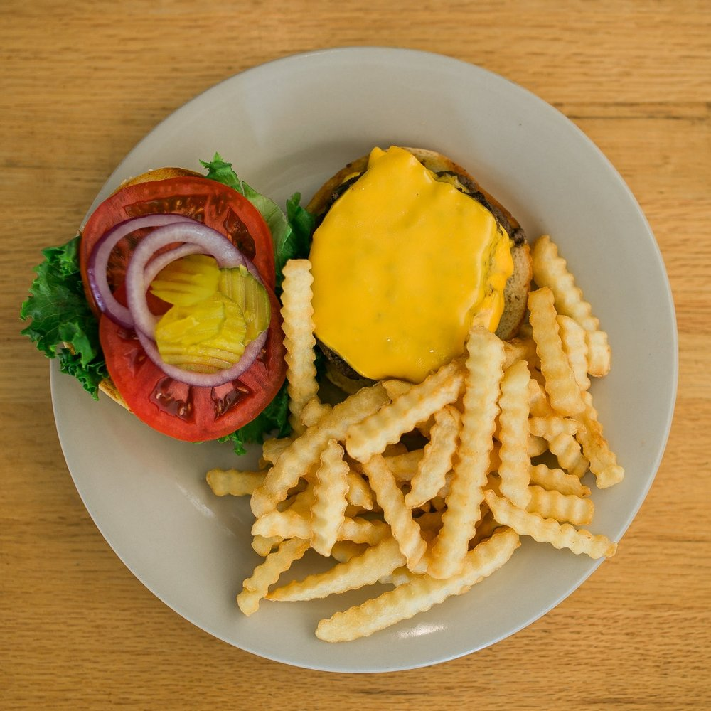 over-head view of a cheeseburger with lettuce, tomato, onions and pickles and a side of crinkle-cut french fries