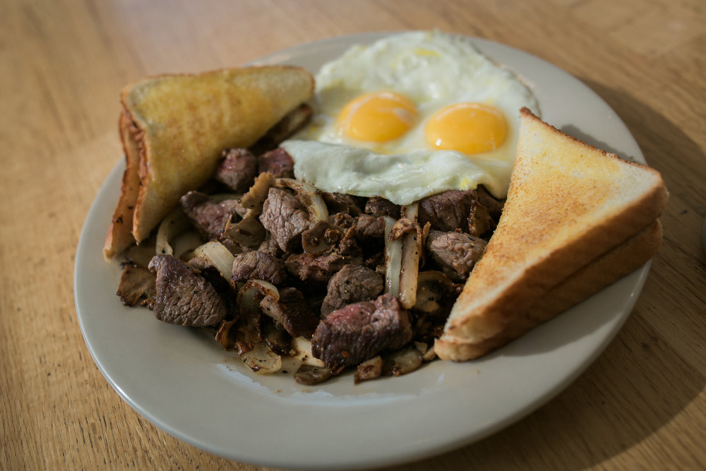a plate of tenderloin beef tips with grilled onions and peppers, sunny-side-up eggs, and buttered white toast