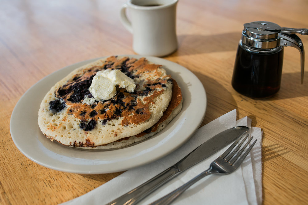 a stack of two blueberry pancakes with butter pads on top fork and knife setting maple syrup and a cup of coffee