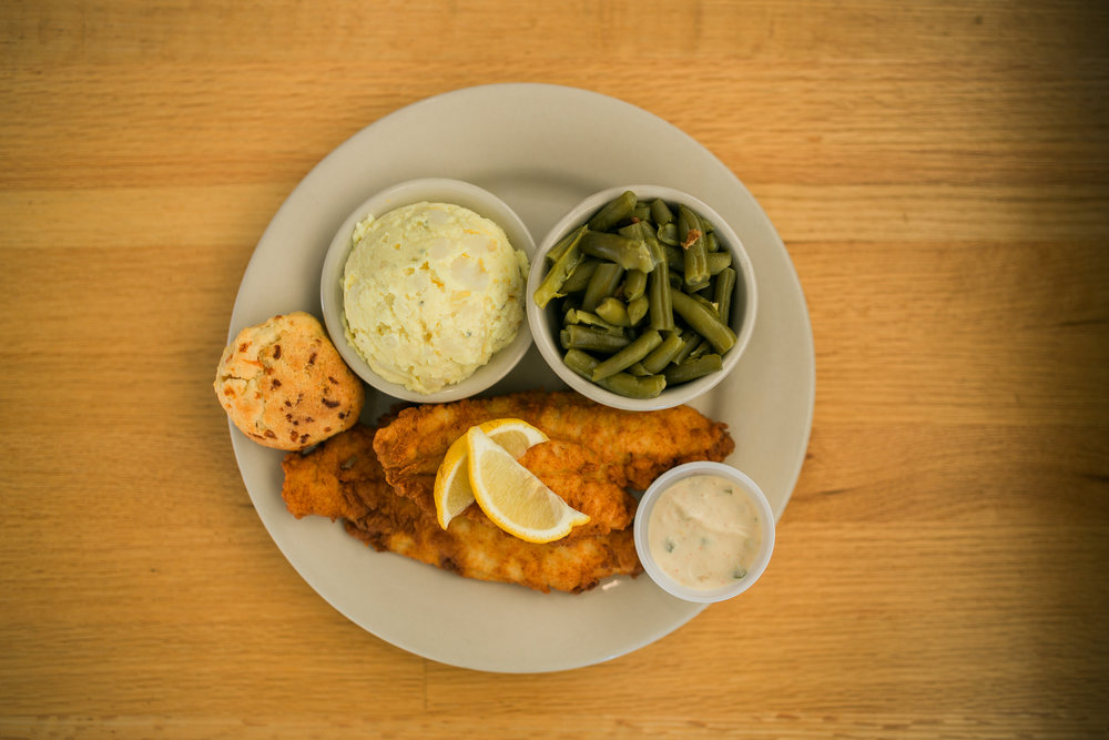 fried catfish topped with lemon slices, mashed potatoes, green beans, tartar sauce, and a cheddar drop biscuit