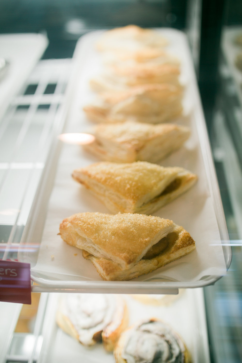 a row of fruit-filled turnovers inside a dessert display