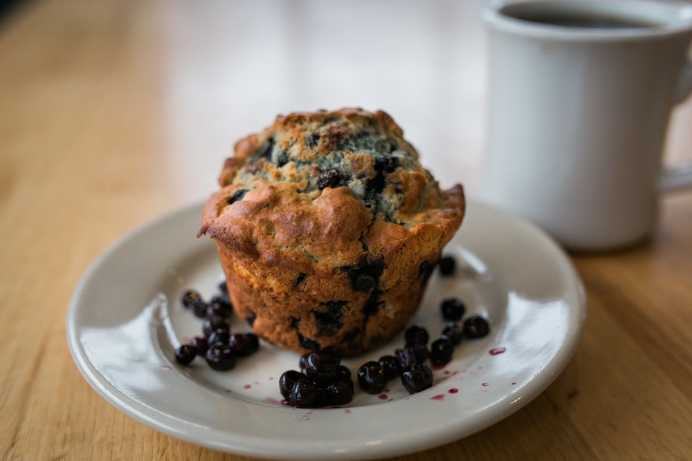 a large bluberry muffin on a saucer surrounded by blueberries and a cup of coffee