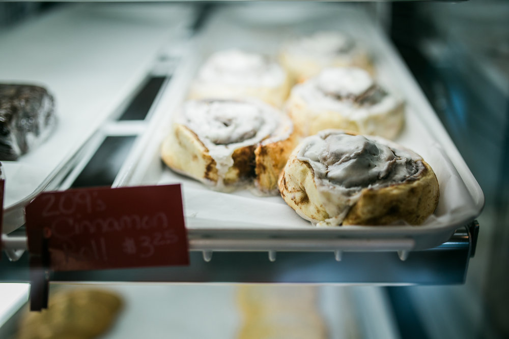 two rows of iced cinnamon rolls inside a dessert display case