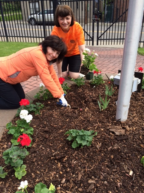 Lisa Lee, CEO of North Point Technology, LLC (left) helps plant flowers during the Endicott Proud Village Clean Up Day  on May 20, 2017.