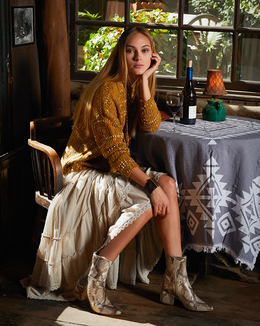 Sweater and boots, AMBIANCE. Skirt, TIENDA HO. Earrings and fringe bag (on table), LOVEBIRD. Necklace, ANTOINETTE. Leather cuff, ROWAN. Gold ring, PLUM GOODS. Throw, RIVIERA TOWEL COMPANY.