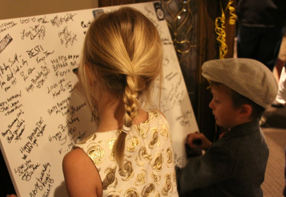 Max and Charlotte signing the poster board.