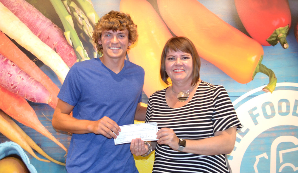 Alec Adair presents a check for $402 for Buddy Packs in Cooper County to The Food Bank Executive Director Lindsay Young Lopez.