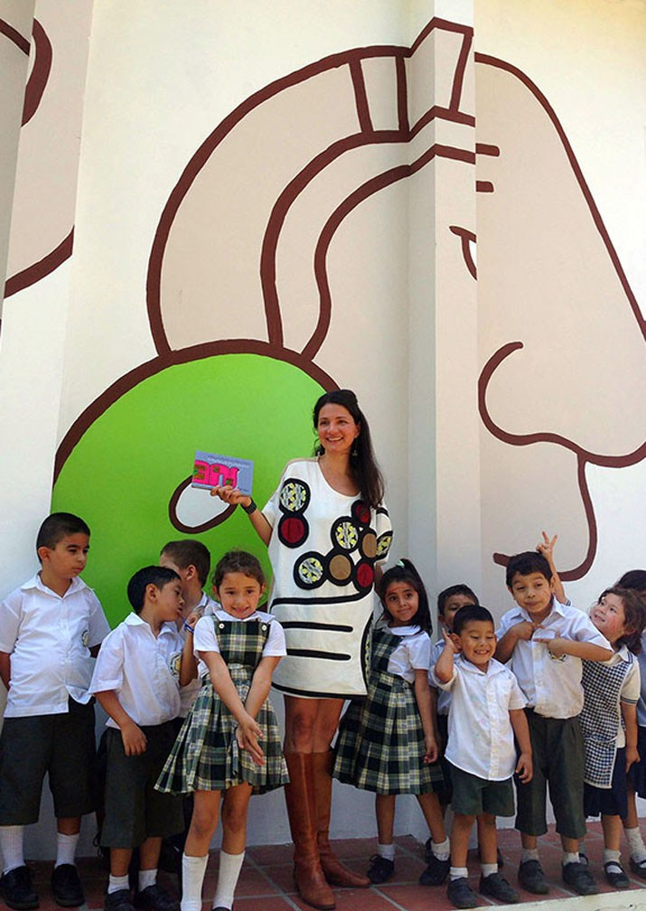 Artist Frida Larios wearing her design while holding her children's book. Photo  Credit