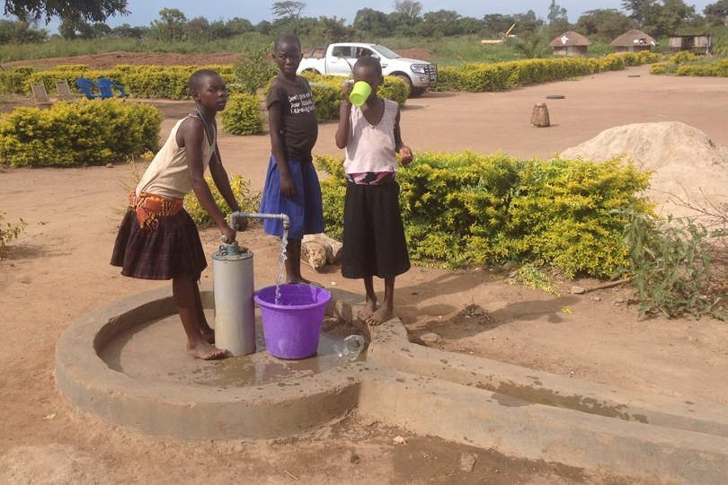 Harriet pumping water at the well with Janet and Prosy. The well is located in front of the dormitory.