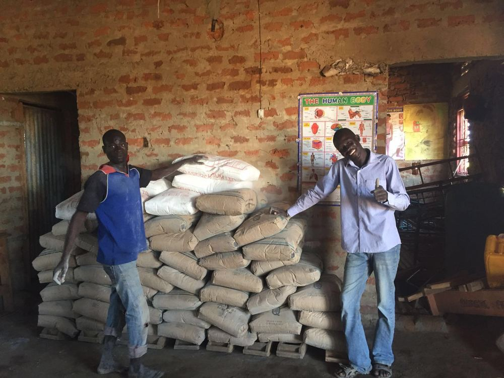 Our founder, Ayella Denis, and one of the builders with bags of concrete.