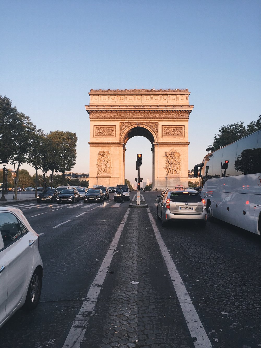 Arc de Triomphe glowing in the morning traffic