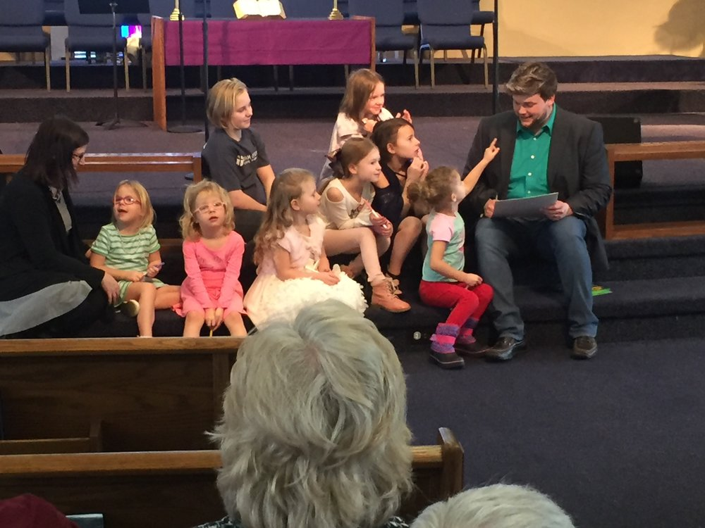 Sarah Hogue, director of children's ministry, and Bud Fickley, director of student ministry, bless some of Dutilh's children during a Sunday service.