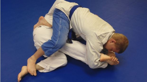 A larger, stronger trainee footlocks his opponent.