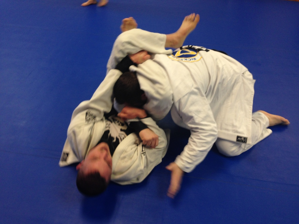 A small trainee uses a leg triangle choke to submit a large opponent