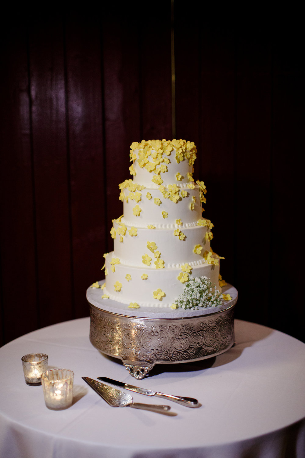 wedding cake with lots of little yellow sugar flowers