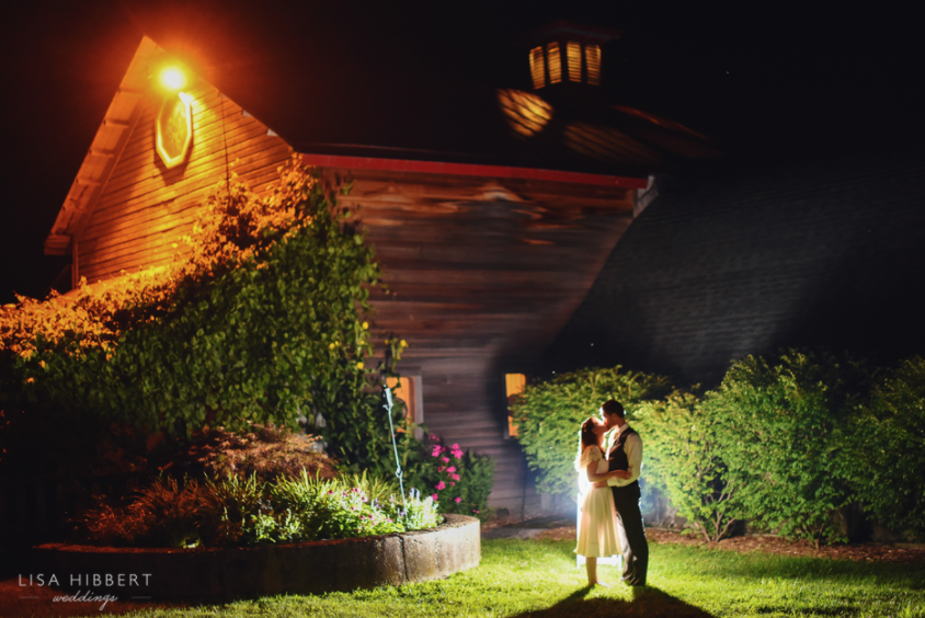 couple outside barn at night