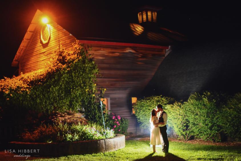 couple outside barn at night