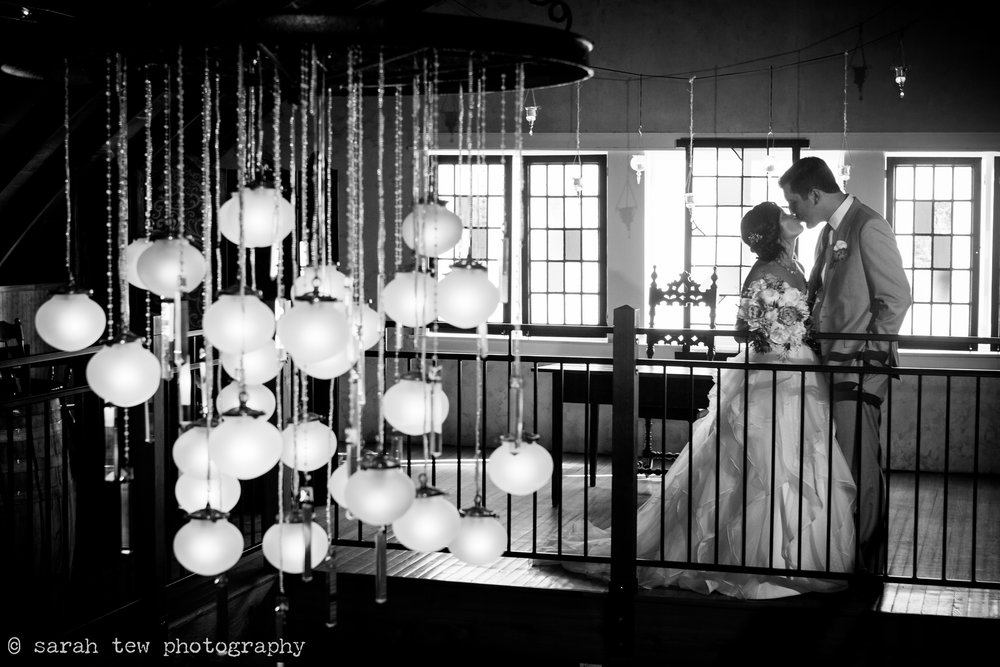 couple kissing in the main barn behind chandelier