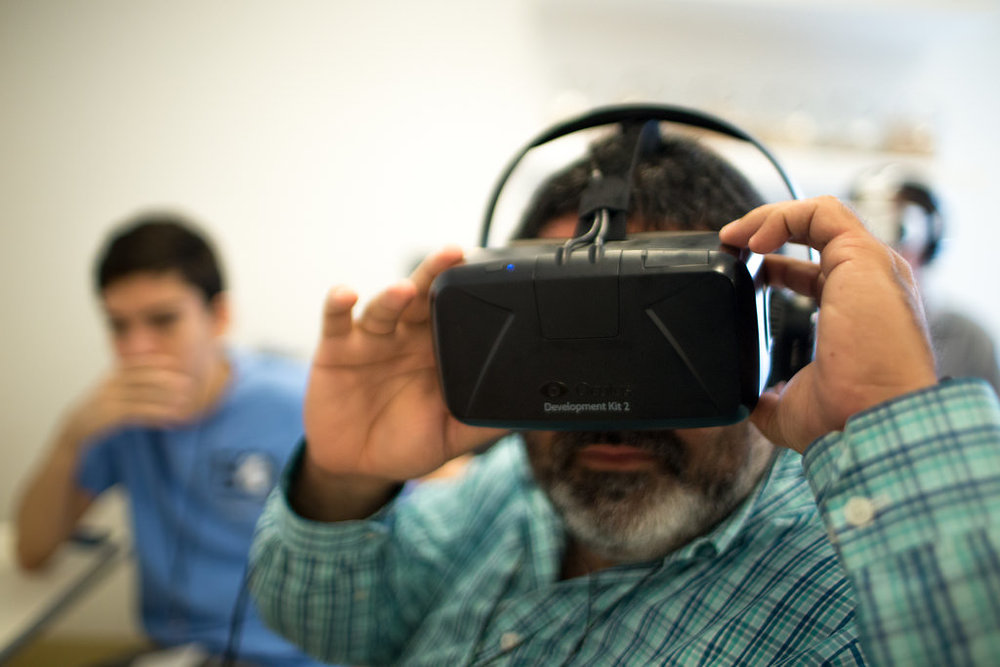 A person wearing virtual reality goggles and another person in the background watching.