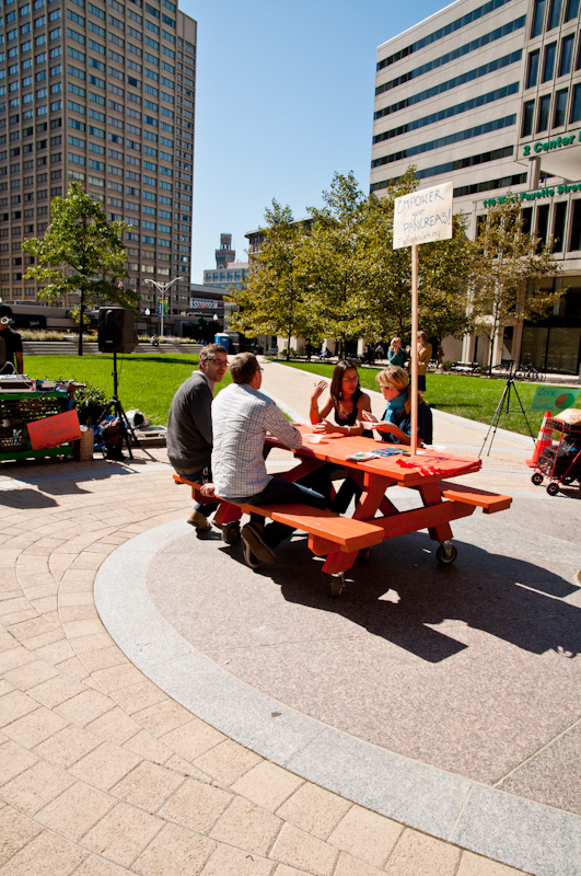 People sitting at the orange table in a city scape setting.