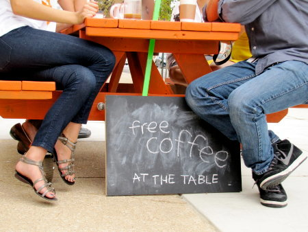Two pairs of feet sitting on on orange picnic table with wheels and a sign that says Coffee _At the Table