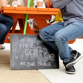 People sitting at an orange picnic table on wheels and a sign that says Coffee _At the Table
