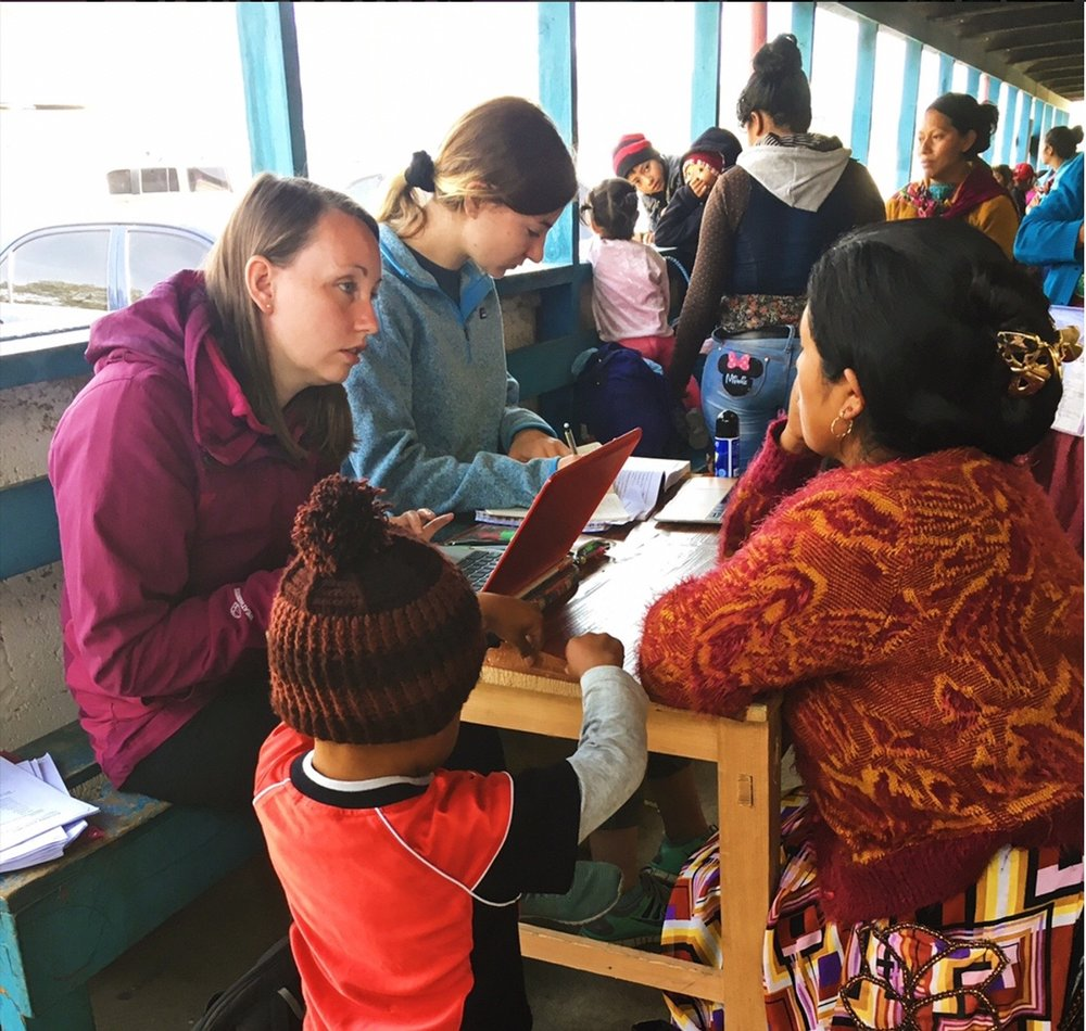 Volunteers Lauren Lambert and Bethan Crisp conducting reproductive health surveys with beneficiaries of the Nutrition Recuperation Program at a medical fair.