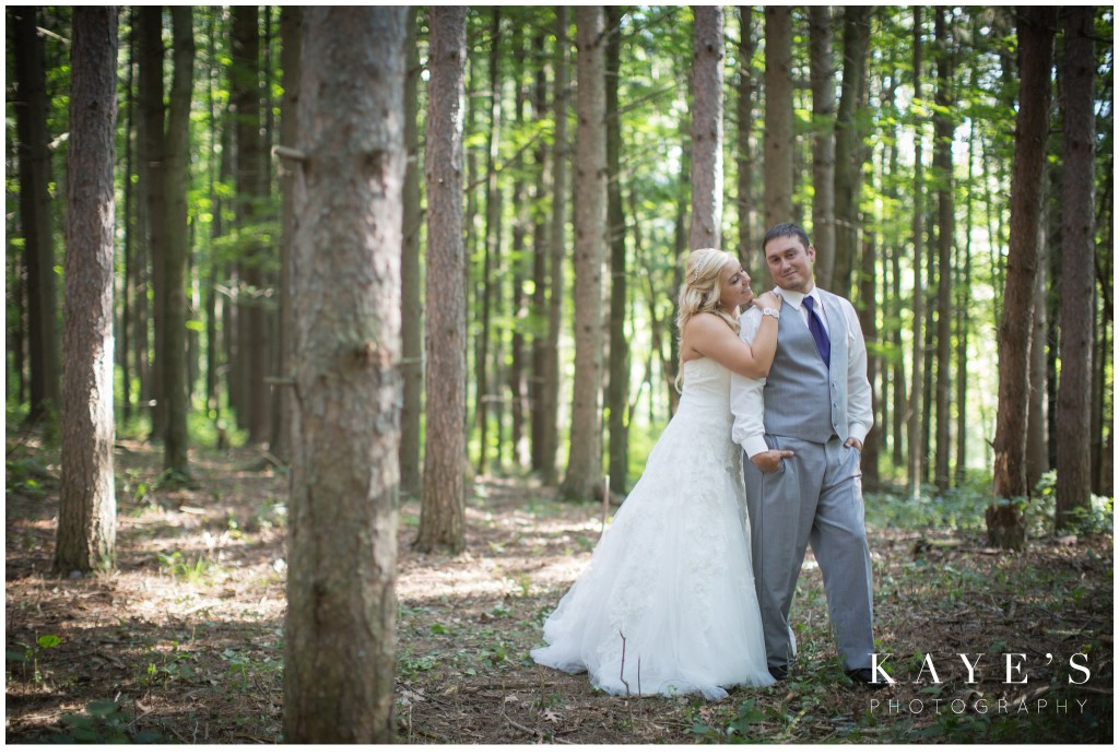 bride and groom in the trees in the wood