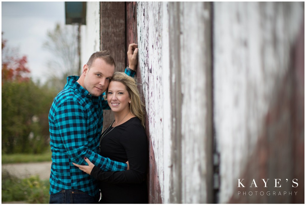 couple cuddling by barn, engagement, heart
