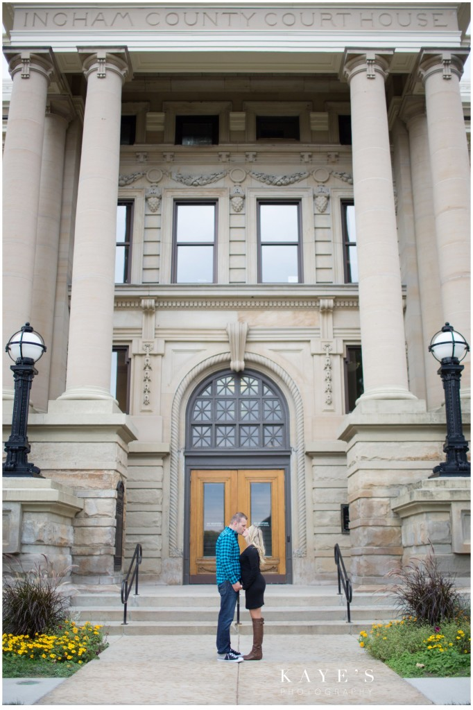 couple kissing in front of building, engagement