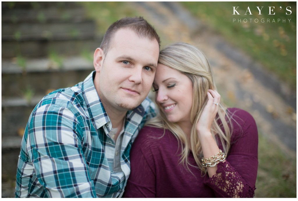 engagement session, couple, cuddle, woman tucking hair behind ear