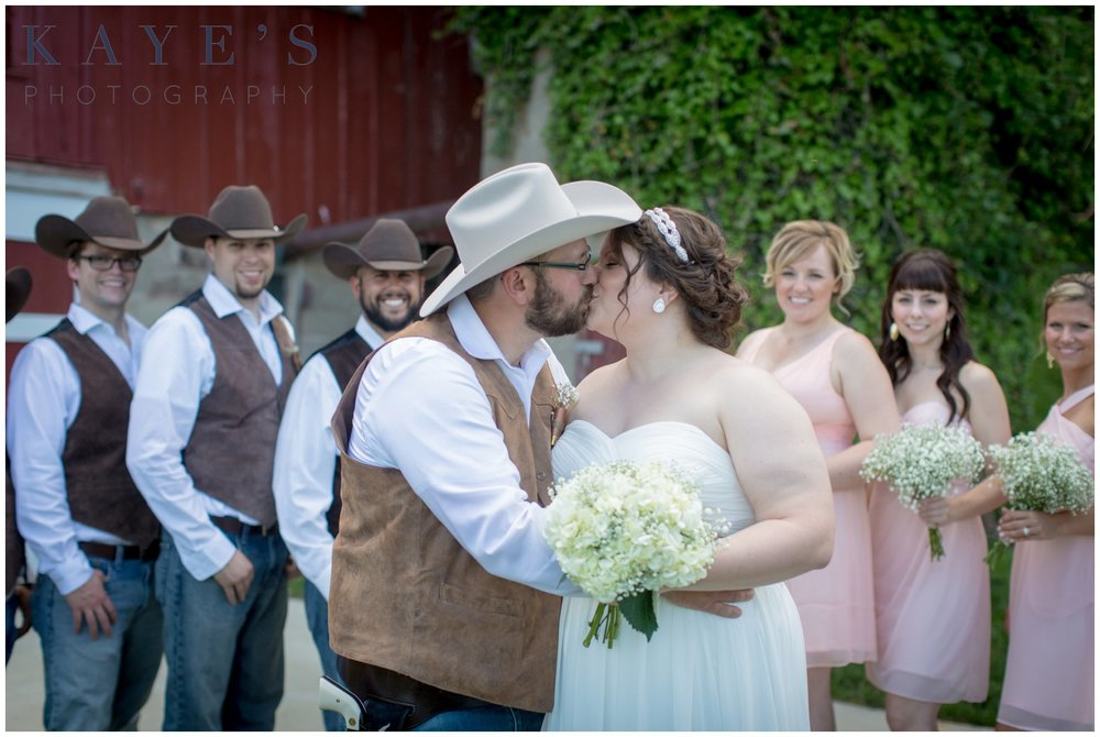 Hudsonville Michigan Wedding Photographer, Hudsonville Michigan Wedding Photography, The Old Wooden Barn Hudsonville Michigan Wedding photography, bride and groom kissing, barn wedding, bride and groom in front of wedding party