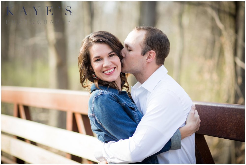 Holly Michigan wedding photography, holly michigan wedding photographer, holly michigan engagement photography, engagement photo, outdoor engagement portraits, portrait photographer, marriage photography, engagement portraits, kissing cheek, couple hugging, couple on bridge