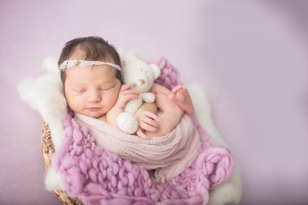 Davison Michigan newborn portrait photographer posing a newborn girl with teddy bear at her studio photo shoot